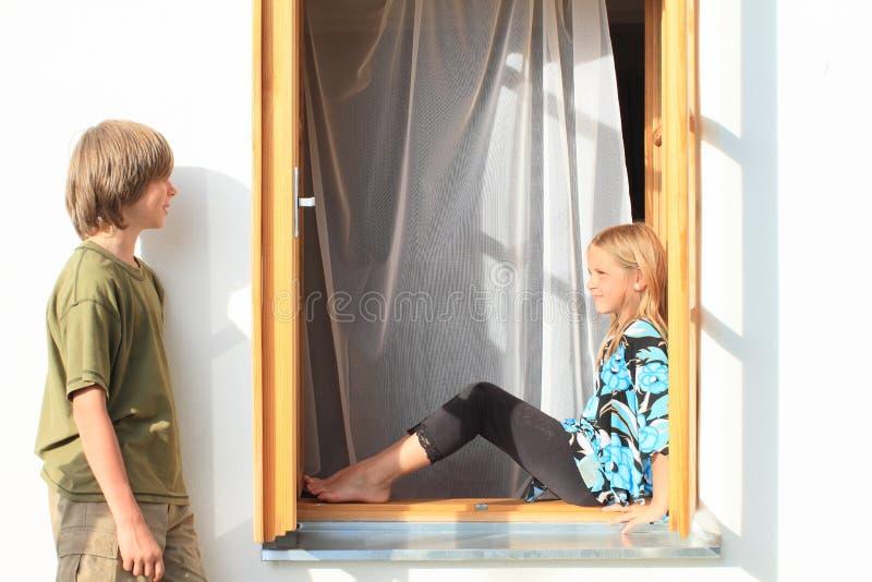 Fille de observation de garçon s'asseyant dans la fenêtre image libre de droits