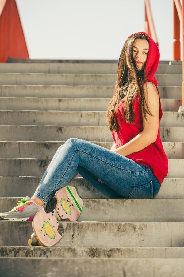 Fille de patin sur des escaliers avec la planche ? roulettes photographie stock libre de droits