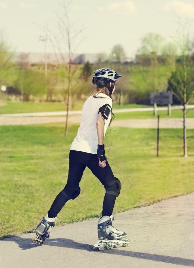 Fille de patinage de rouleau en stationnement rollerblading sur les patins intégrés image libre de droits
