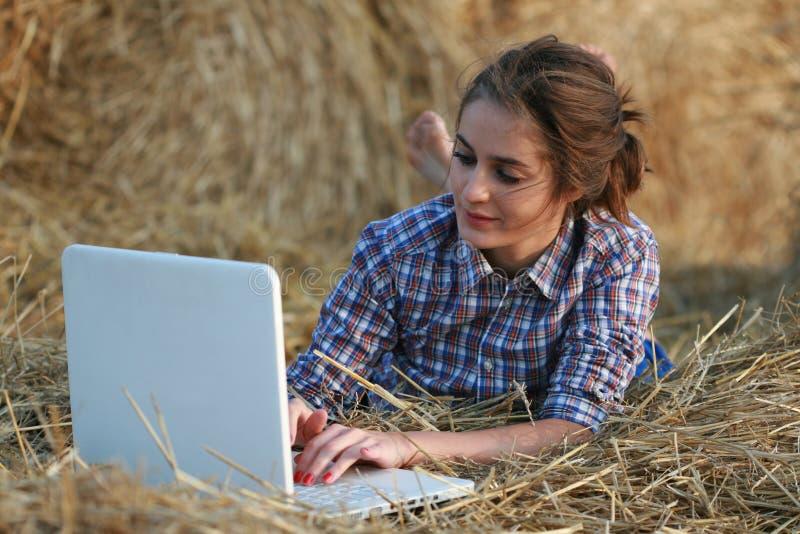 Fille de pays se trouvant sur le foin avec l'ordinateur portatif photos libres de droits