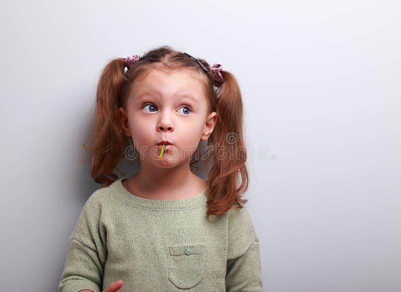 Fille de pensée drôle d'enfant mangeant la lucette et recherchant images libres de droits