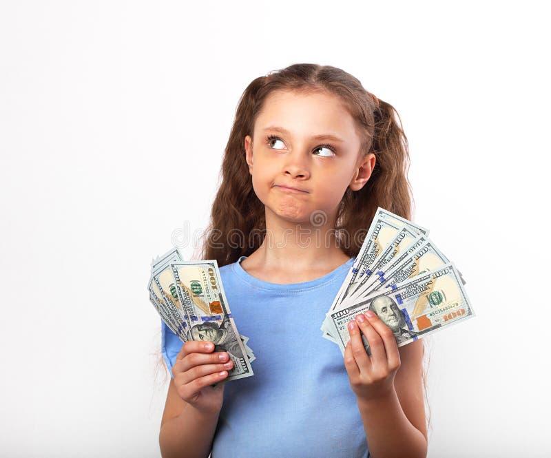 Fille de pensée grimaçante heureuse d'enfant de doute tenant l'argent dans le Han photo stock