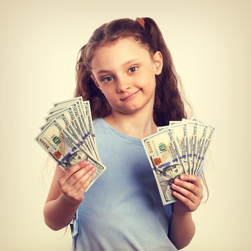 Fille de pensée grimaçante heureuse d'enfant de doute tenant l'argent dans le Han images stock