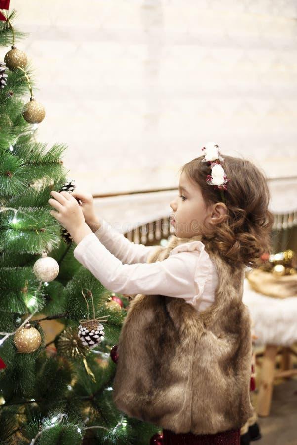 Fille de petit enfant décorant l'arbre de Noël avec des boules à la maison, à l'intérieur Fin vers le haut Concept de Noël images stock
