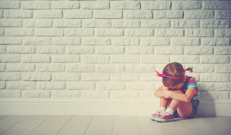 Fille de petit enfant pleurant et triste au sujet du mur de briques image libre de droits