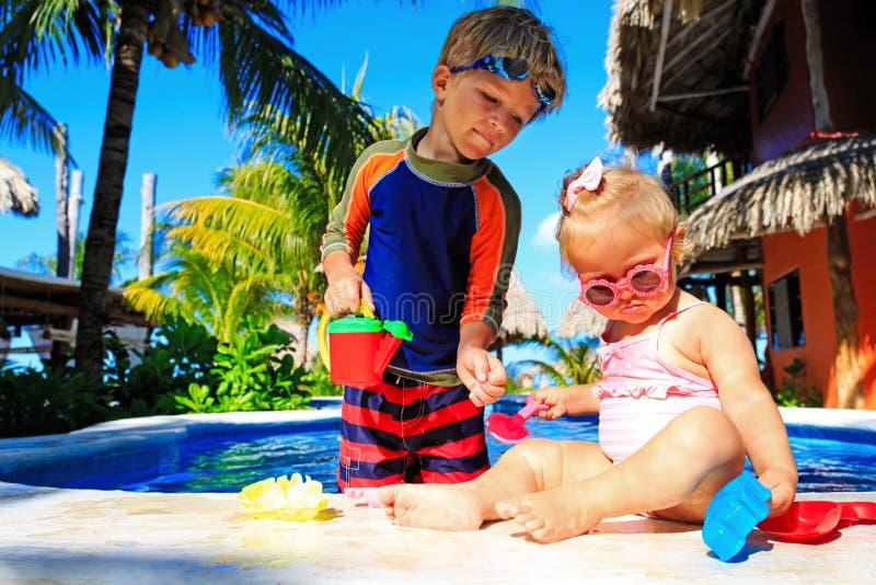 Fille de petit garçon et d'enfant en bas âge jouant dans la natation images libres de droits