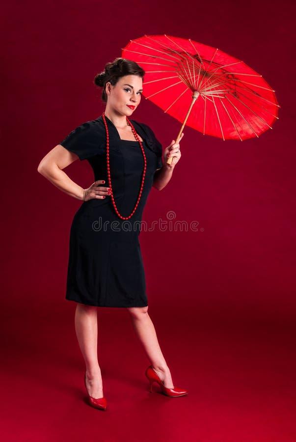 Fille de pin-up avec le parapluie rouge photo stock