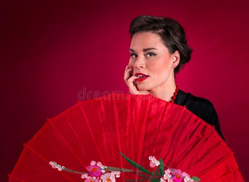 Fille de pin-up dans la robe noire au-dessus du parasol rouge images stock