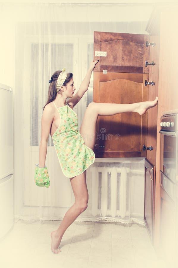 Fille de pin-up de jeune belle femme séduisante sportive flexible à la cuisine photographie stock libre de droits