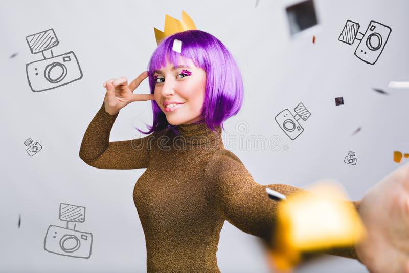 Fille de portrait de Selfie jolie avec la coupe de cheveux violette ayant l'amusement en tresse d'or Elle a la couronne d'or, sou photographie stock libre de droits