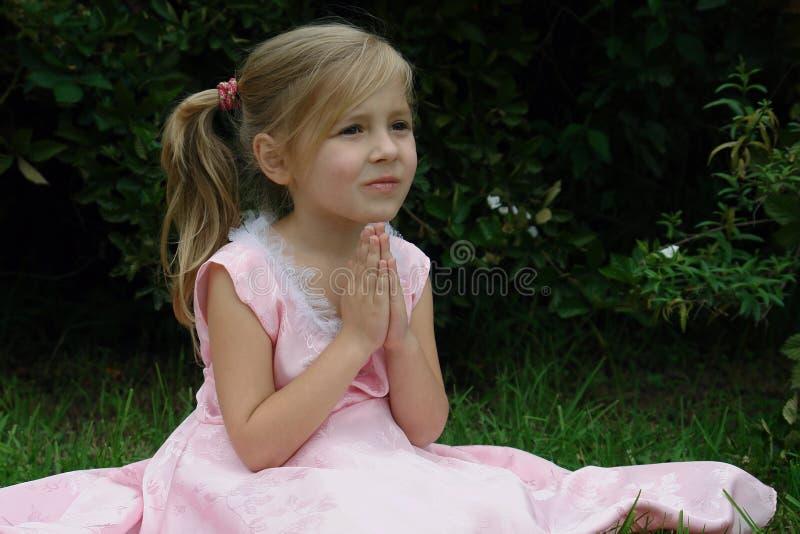 Fille de prière sur l'herbe images stock
