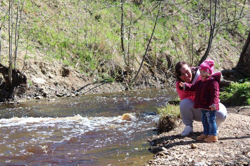 Fille de promenade avec sa mère sur la nature près de l'eau image stock