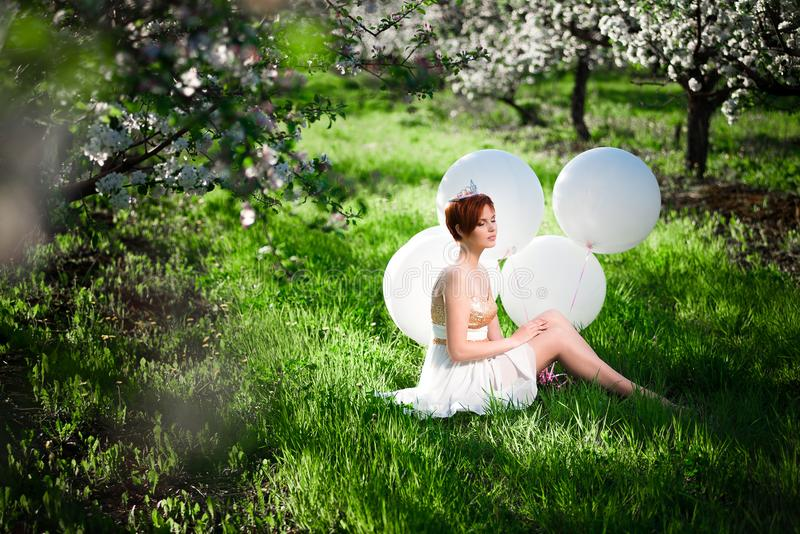 Fille de rêve sur une herbe verte avec les ballons à air massifs photographie stock libre de droits