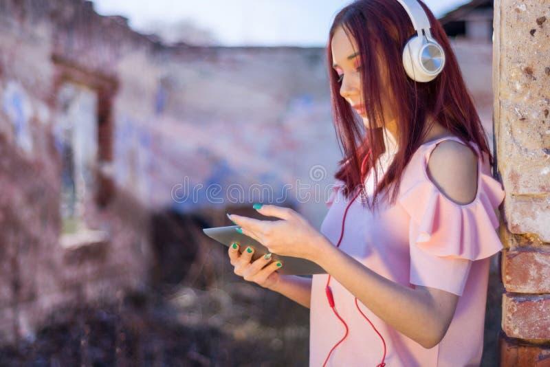 Fille de Redheads avec des écouteurs dans les ruines de la maison écoutant la musique sur le comprimé numérique photos libres de droits