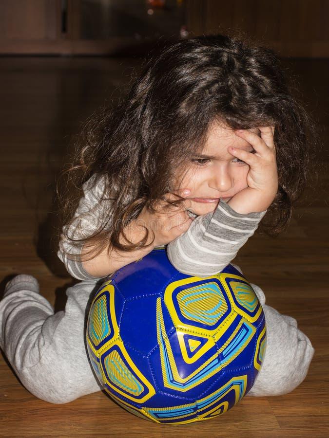 Fille de renversement avec une boule portrait de fille de quatre ans image stock