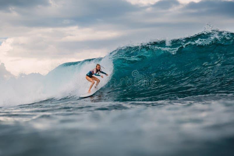 Fille de ressac sur la planche de surf Femme de surfer et vague bleue photo libre de droits