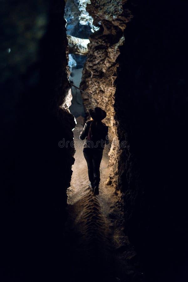 Fille de silhouette explorant la caverne énorme Le voyageur d'aventure a habillé le chapeau de cowboy et le sac à dos, veste en c image stock