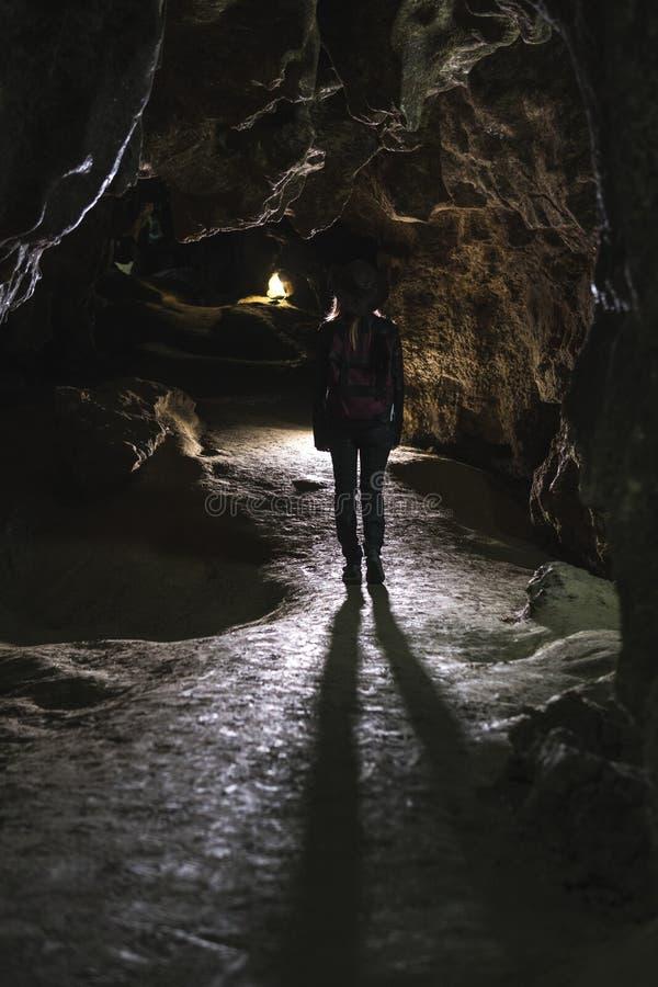 Fille de silhouette explorant la caverne énorme Le voyageur d'aventure a habillé le chapeau de cowboy et le sac à dos, veste en c images libres de droits