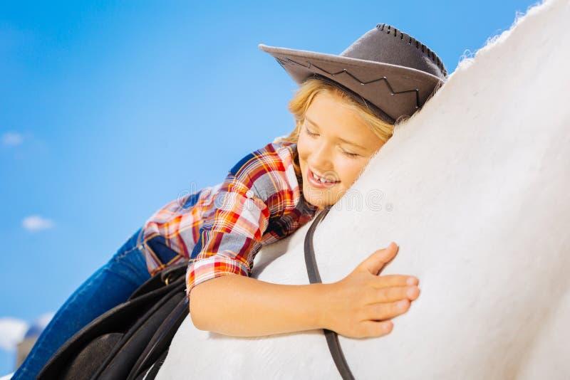 Fille de soin mignonne de cowboy étreignant son cheval blanc préféré images libres de droits