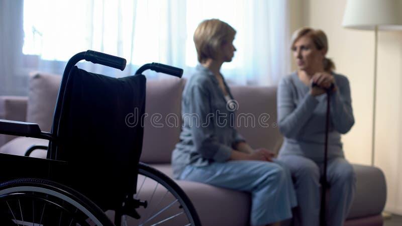 Fille de soin parlant avec la mère supérieure handicapée à la maison, réadaptation images libres de droits