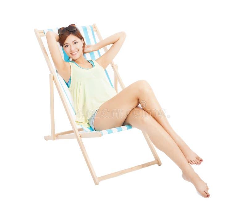 Fille de soleil de beauté souriant et se trouvant sur une chaise de plage photos stock