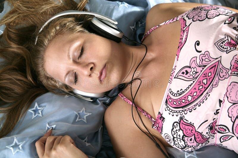 Fille de sommeil avec l'écouteur photographie stock