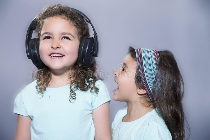 Fille de sourire écoutant la musique dans des écouteurs avec le cri perçant de soeur images libres de droits