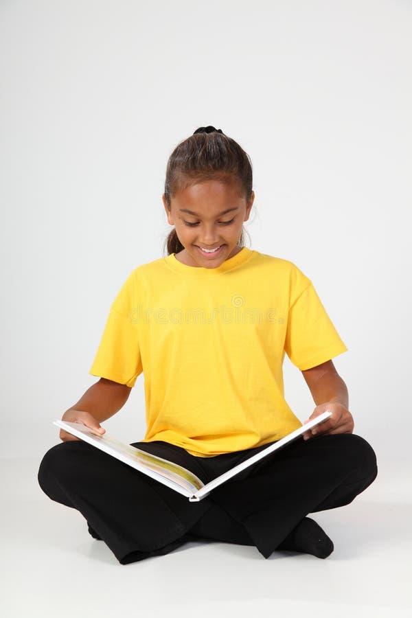 Fille de sourire 10 d'école s'asseyant affichant un goujon de livre image libre de droits