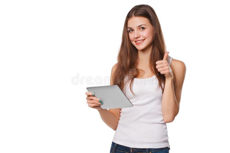 Fille de sourire attirante dans la chemise blanche utilisant le comprimé montrant des pouces  Femme avec le PC de comprimé, d'iso images libres de droits