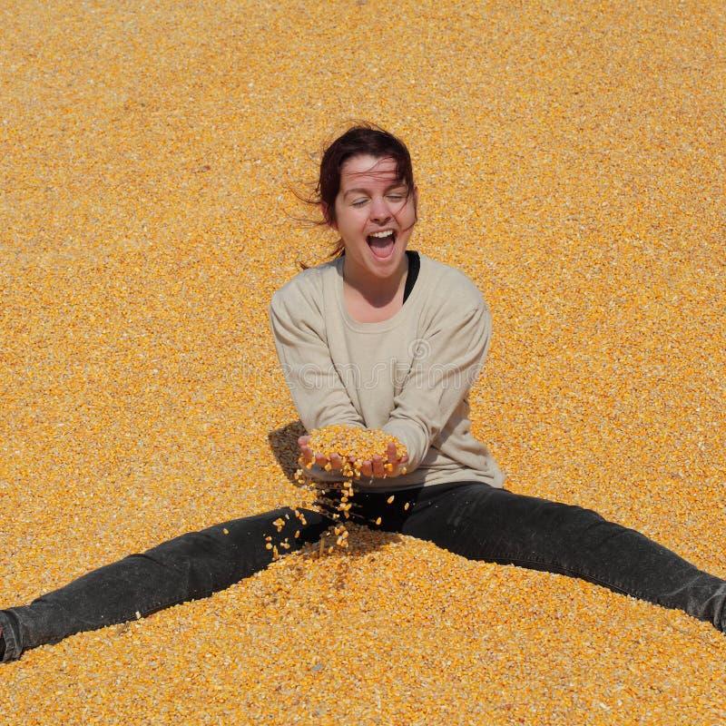 Fille de sourire au tas du maïs après récolte photos stock