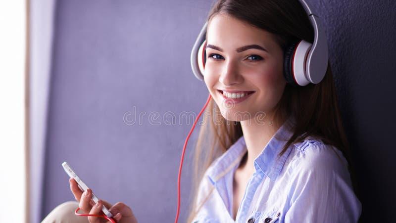 Fille de sourire avec des écouteurs se reposant sur le plancher photos libres de droits