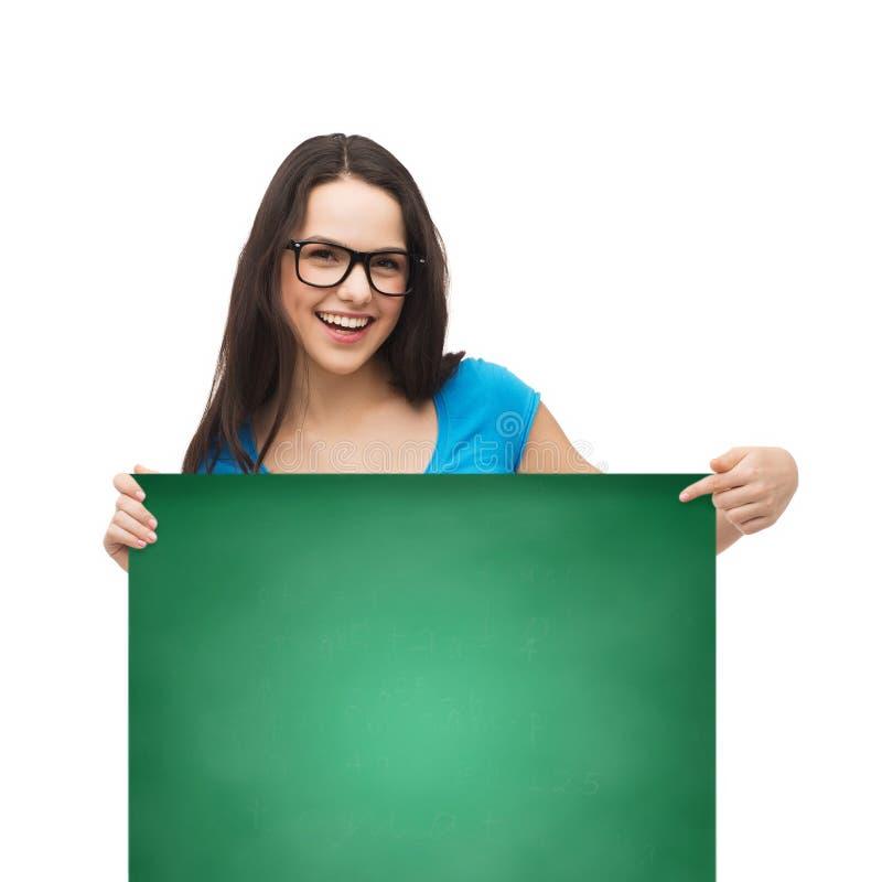 Fille de sourire avec des lunettes et conseil vide blanc photo stock