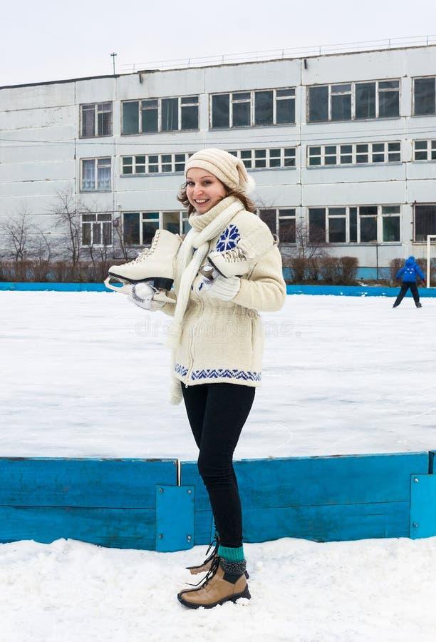 Fille de sourire avec des manies sur la piste de patinage de glace images libres de droits