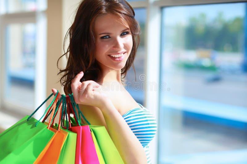 Fille de sourire avec des paniers dans la boutique photographie stock libre de droits