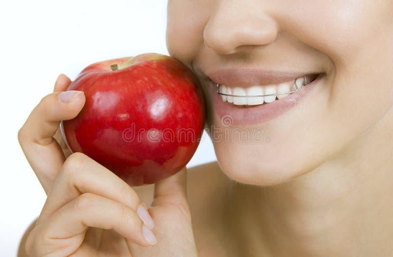Fille de sourire avec l'arrêtoir pour les dents et la pomme image libre de droits