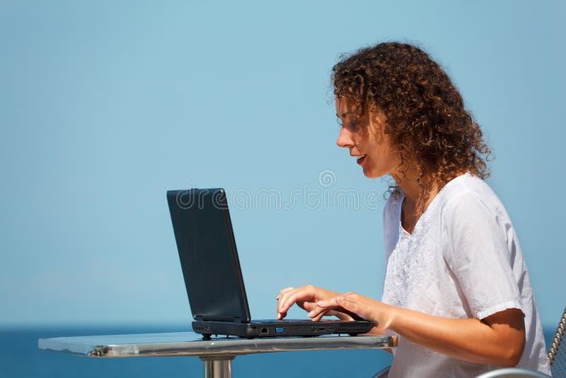 Fille de sourire avec l'ordinateur portatif. Se repose à la table sur la plage photos libres de droits