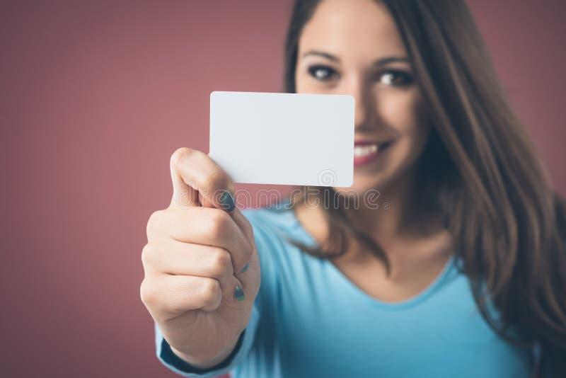 Fille de sourire avec la carte de visite professionnelle de visite photographie stock libre de droits
