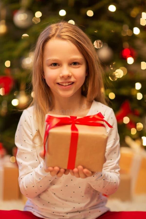 Fille de sourire avec le cadeau de Noël à la maison images libres de droits