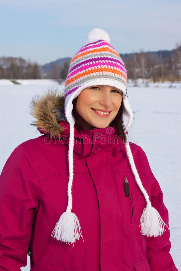 Fille de sourire avec le capuchon de l'hiver photo libre de droits