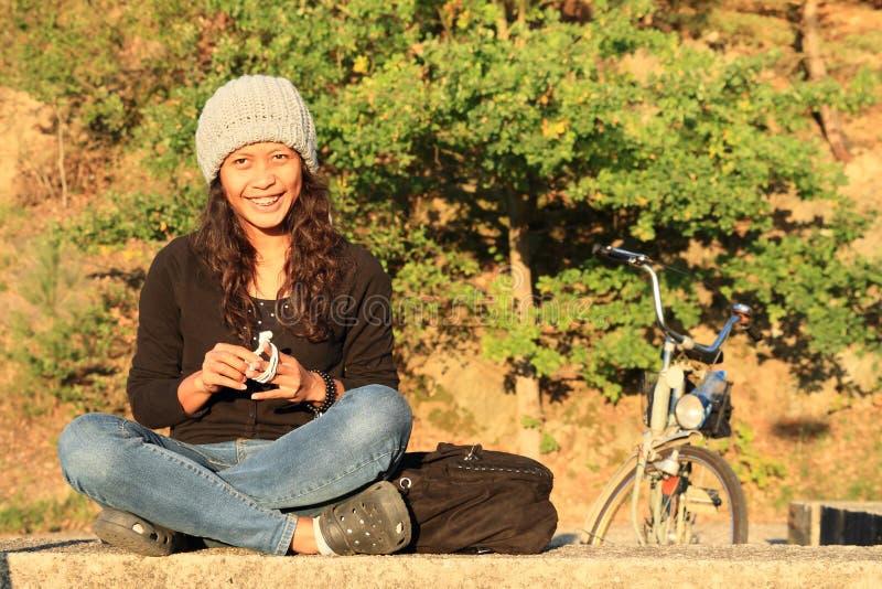 Fille de sourire avec le vélo derrière image libre de droits