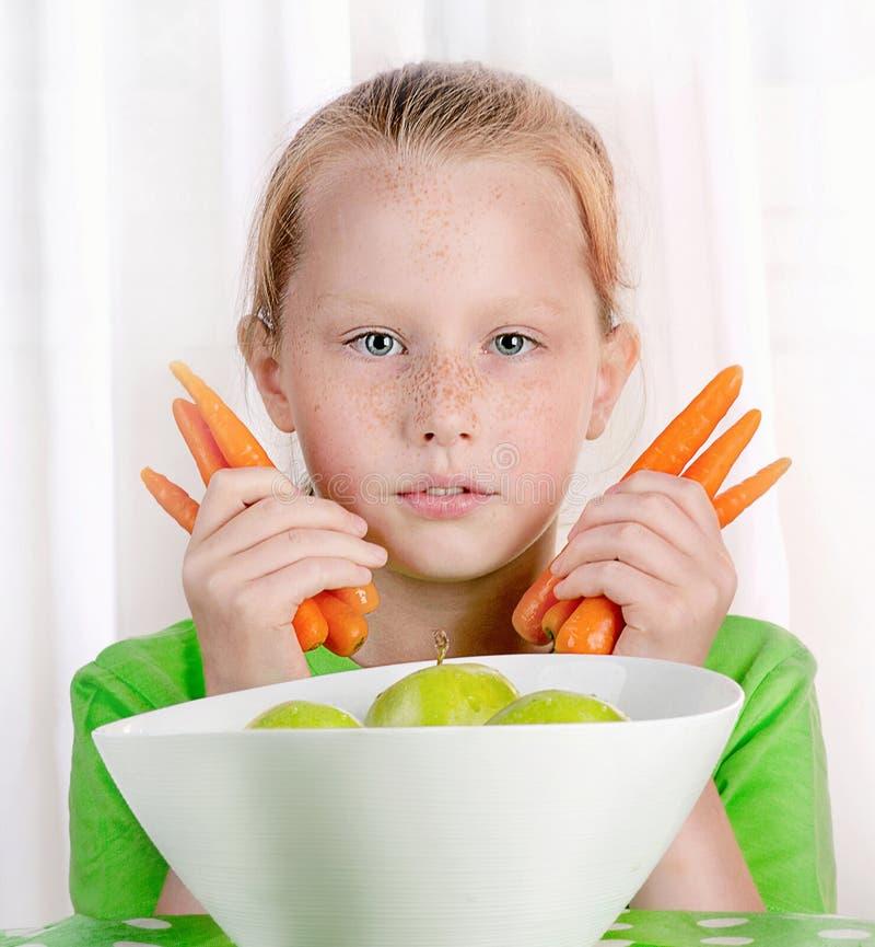 Fille de sourire avec les pommes et les carottes vertes fraîches image libre de droits