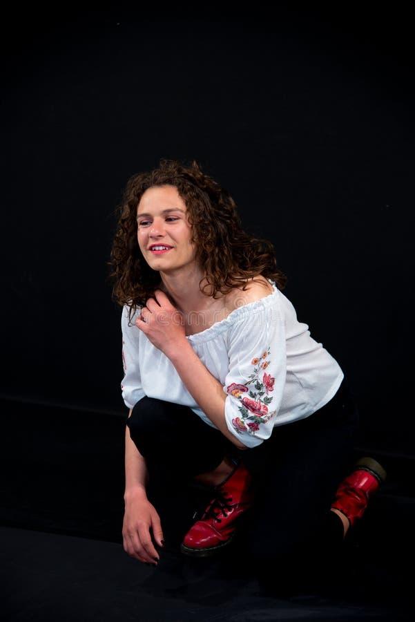 Fille de sourire bouclée de belle brune Espadrilles rouges photographie stock