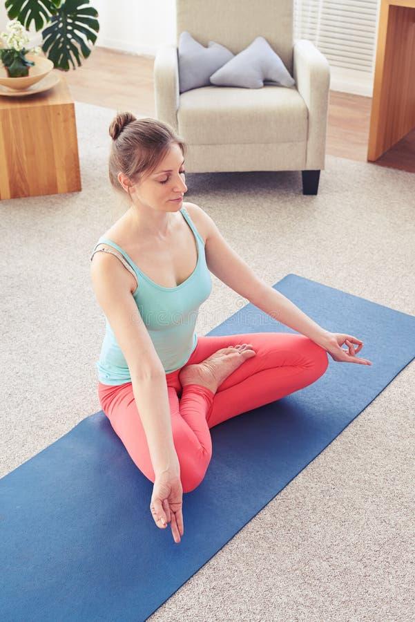 Fille de sourire décontractée faisant la posture de lotus sur le tapis de yoga image stock