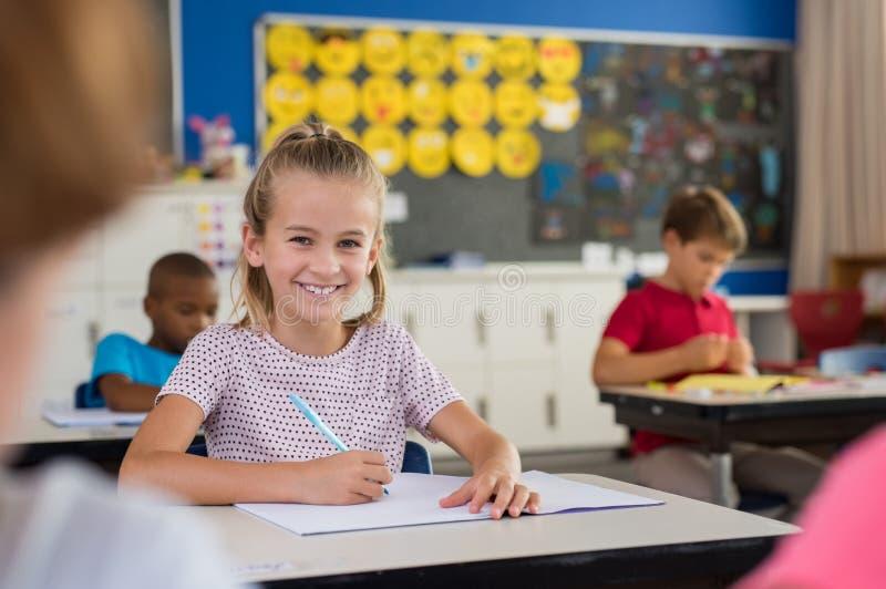 Fille de sourire d'école prenant des notes photographie stock