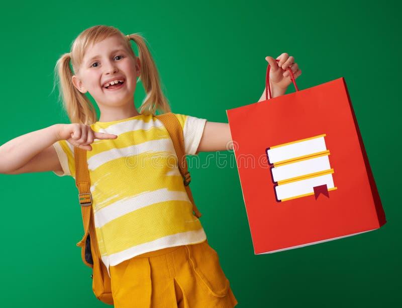 Fille de sourire d'école se dirigeant au sac à provisions avec la papeterie images libres de droits