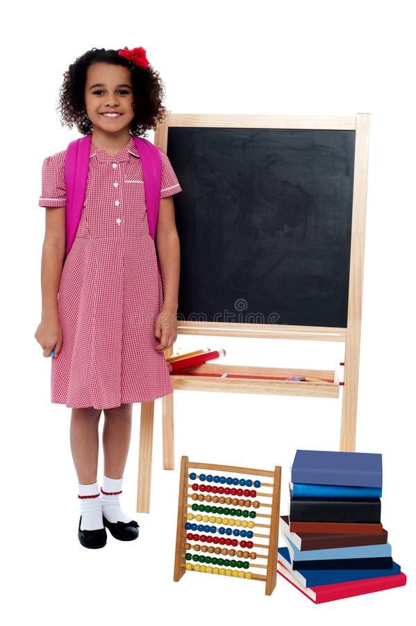 Fille de sourire d'école se tenant près du tableau noir images libres de droits