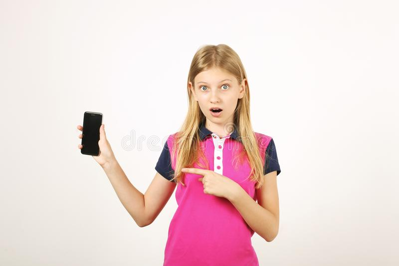 Fille de sourire d'adolescent dans l'équipement occasionnel posant avec le téléphone portable, montrant des émotions, faisant les photos stock