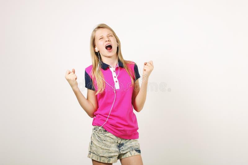Fille de sourire d'adolescent dans l'équipement occasionnel posant avec le téléphone portable, montrant des émotions, faisant les photographie stock