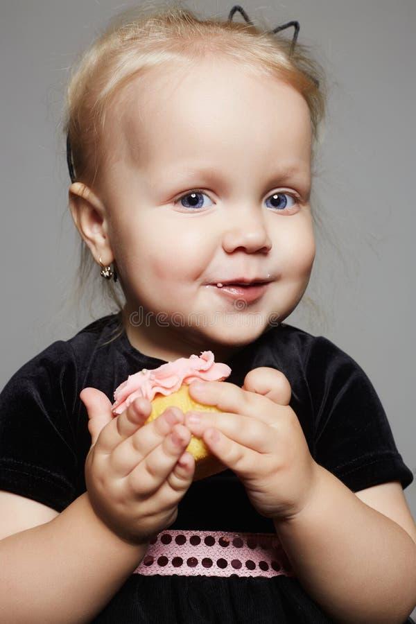 Fille de sourire d'enfant de bébé avec le gâteau de sucre photographie stock libre de droits