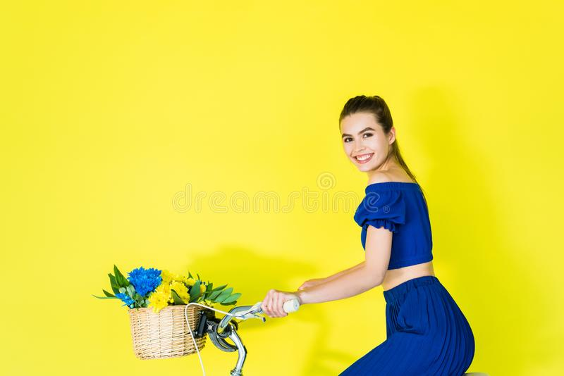 Fille de sourire dans la bicyclette bleue d'équitation de robe sur le bleu photo libre de droits